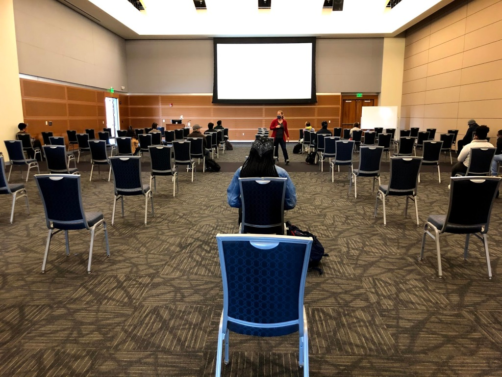 Picture of nearly empty ballroom lined with chairs